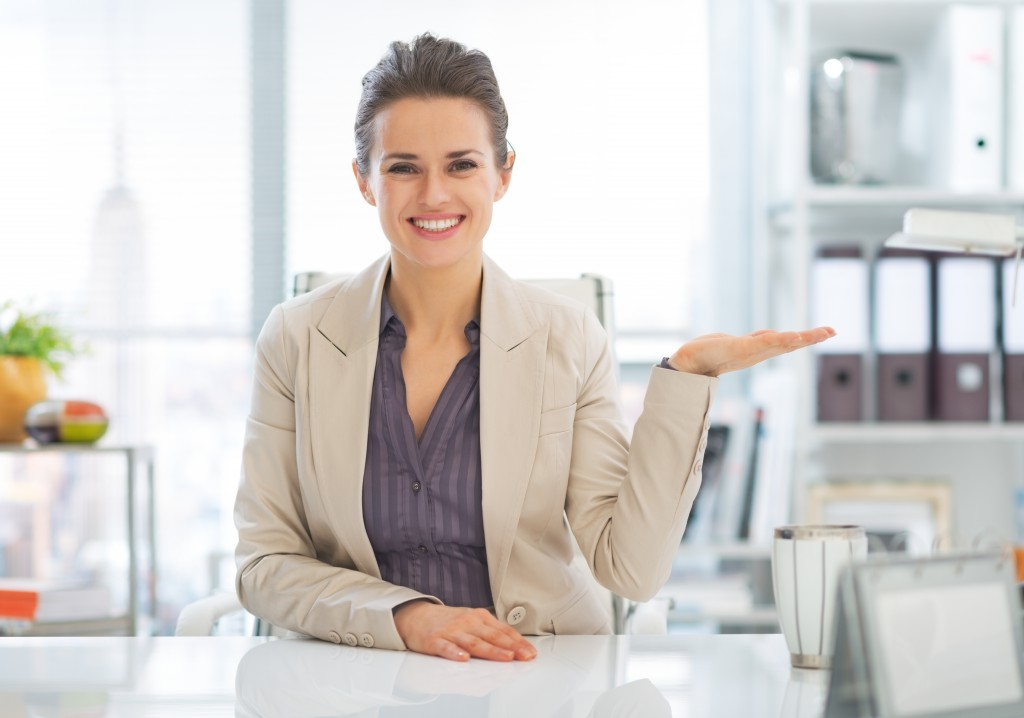 Happy business woman presenting something on empty palm in office